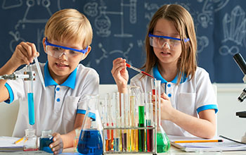 A boy and a girl pour liquid in a test tube using pipette.  Multiple test tubes on the table with colorful liquids inside