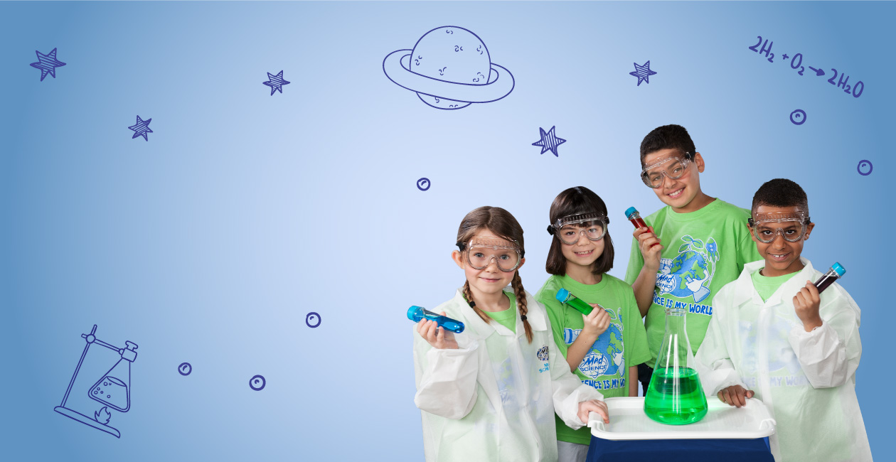 2 kids in lab coats, 2 in green t shirts holding test tubes with different color liquid inside. A beaker with a green liquid.