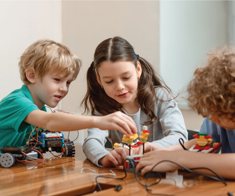 3 children building a Lego based electric toy cart